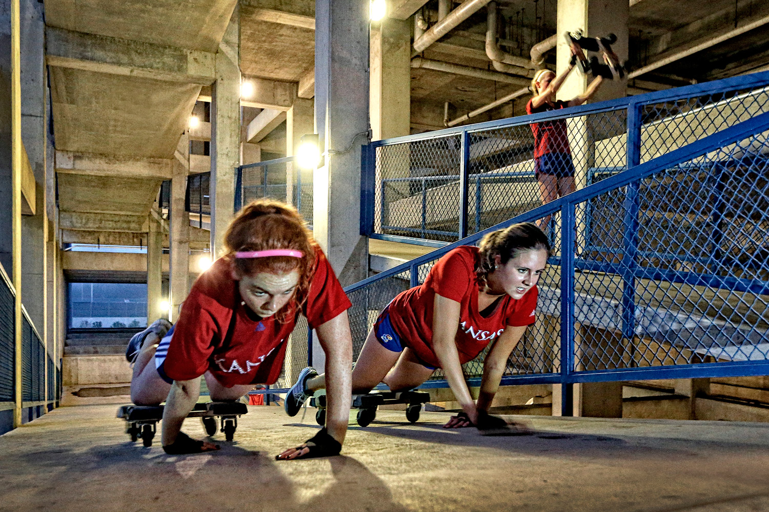 Sammie Schurig and Madison Straight pull themselves up a ramp at Memorial Stadium